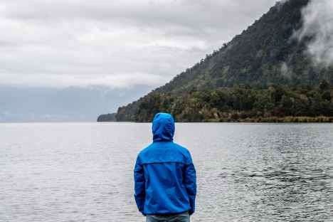 person wearing blue hoodie near body of water