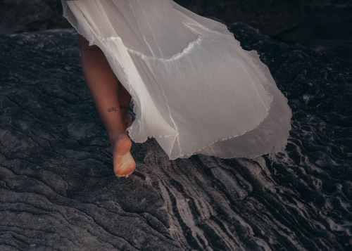 woman wearing white dress walking on sand